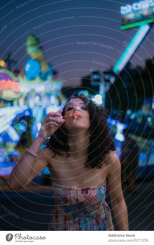 Frau im Vergnügungspark bläst Blasen Schaumblase Schlag Sommer Spaß Freizeit brünett genießen jung Abend schön Feiertag Urlaub Anziehungskraft unterhalten
