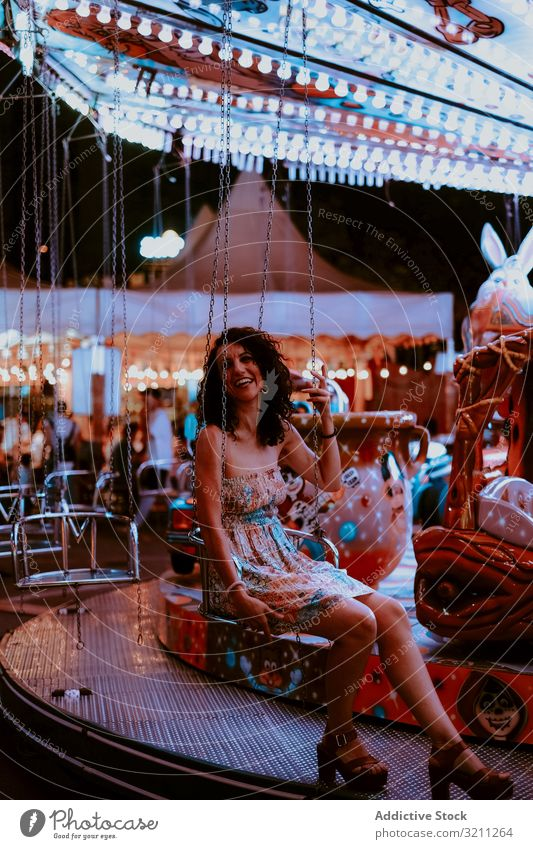 Frau genießt die Fahrt auf dem Karussell Vergnügungspark Mitfahrgelegenheit Sommer heiter Abend Spaß Freizeit brünett genießen Glück jung schön Feiertag Kleid