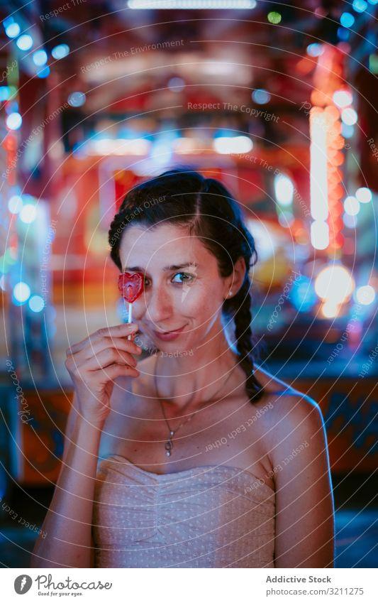 Frau mit Lolli im Vergnügungspark Jahrmarkt Lollipop sich[Akk] entspannen Sommer heiter Spaß Lächeln Freizeit Abend dunkel genießen Glück lässig jung schön