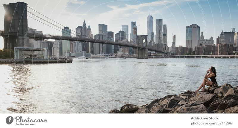 Frau, die auf Felsen in Brooklyn sitzt und an einem sonnigen Tag auf die Brücke und Manhattan schaut Großstadt Ansicht Fluss Wolkenkratzer Architektur Gebäude
