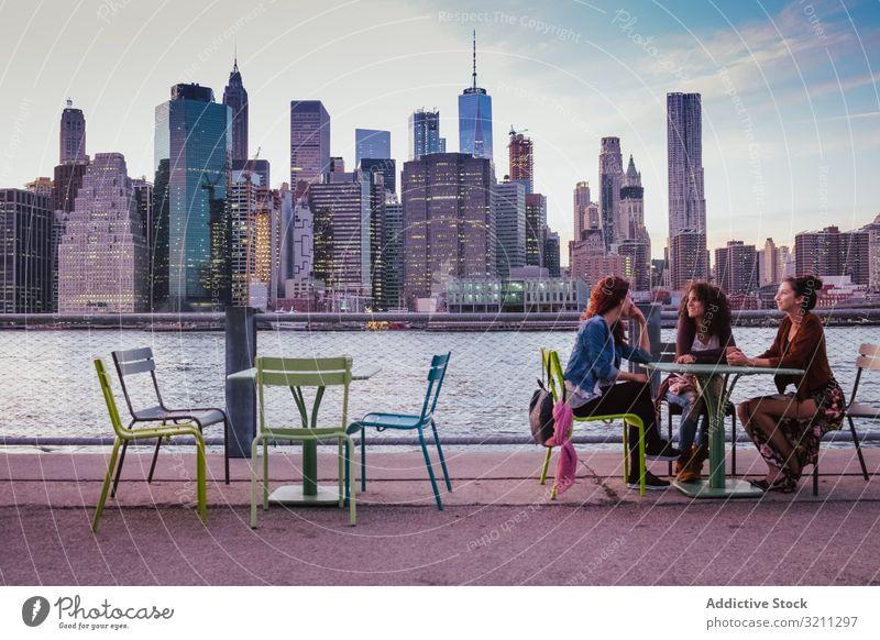 Freunde sitzen abends auf der Terrasse mit New Yorker Hintergrund Großstadt Ansicht Brücke Fluss Wolkenkratzer Architektur Gebäude Stadtbild reisen modern urban
