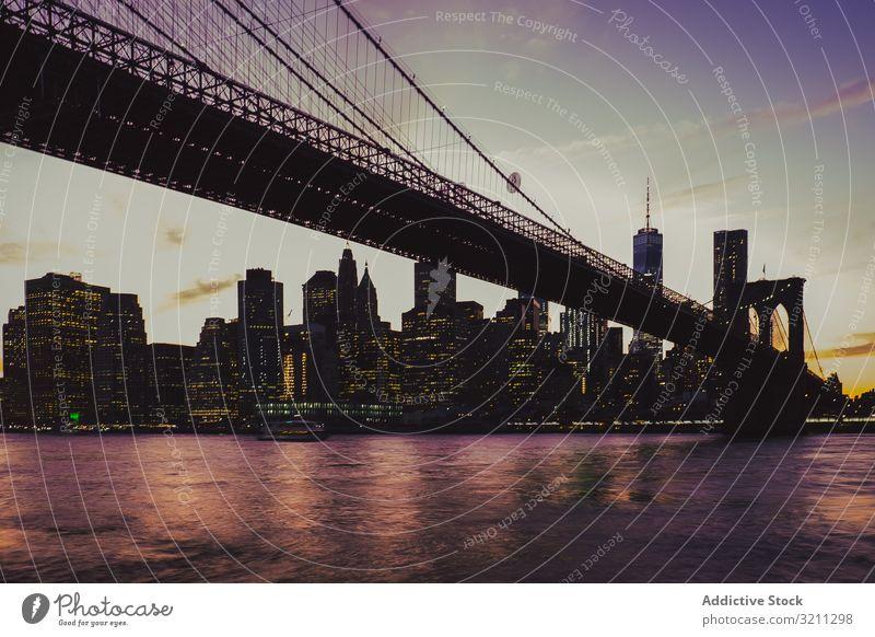 Brooklyn-Brücke am Abend mit Manhattan-Landschaft im Hintergrund Großstadt Ansicht beleuchtet Fluss Wolkenkratzer Architektur Gebäude Stadtbild reisen Nacht