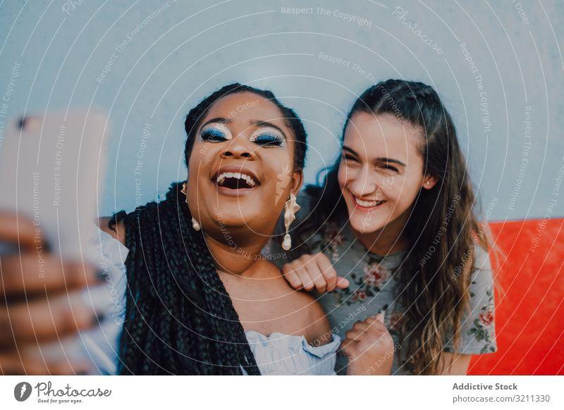 Lächelnde multiethnische Frauen, die Selbsthilfe nehmen Selfie nehmen Lachen Smartphone sitzen Sofa modern trendy Inhalt attraktiv hell rassenübergreifend