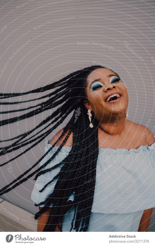 Fröhliche, trendige afroamerikanische Frau mit fliegenden Haaren fliegendes Haar Glück trendy Lächeln modern attraktiv Zopf umdrehen Straße Inhalt stehen