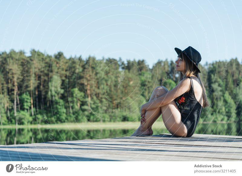 Junge Frau sitzt auf dem Pier in der Natur bewundernd See Freiheit reisen Tourismus ruhen Abenteuer Wald Tourist malerisch jung Glück Freude ländlich Ansicht
