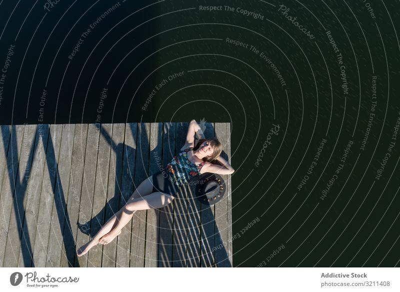 Junge Frau am Pier liegend in der Natur See sich[Akk] entspannen entspannt reisen Tourismus ruhen Abenteuer Wald malerisch Freude ländlich Ansicht genießen