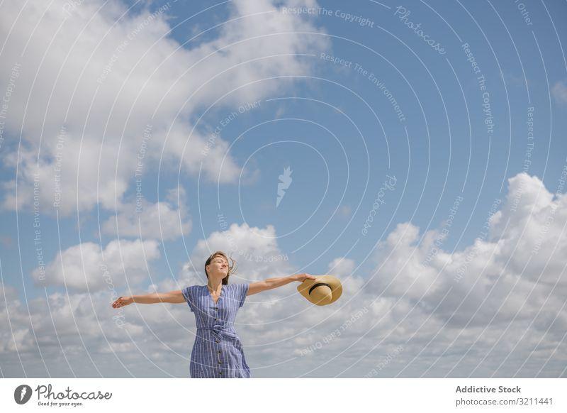 Fröhliche junge Frau genießt die Brise genießend Glück sorgenfrei Freiheit Wind Sonnenkleid Sommer Spaziergang fliegendes Haar Windstille Strohhut positiv