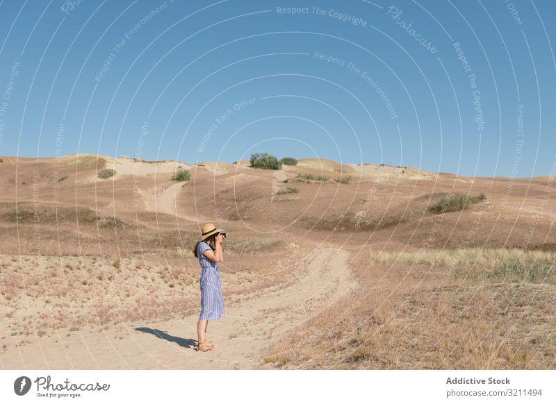Junge Fotografin auf trockenem Feld Spaziergang Frau Straße Sand Landschaft Fotokamera Nachlauf ungepflastert trocknen staubig Gras sonnig Einsamkeit Sommer