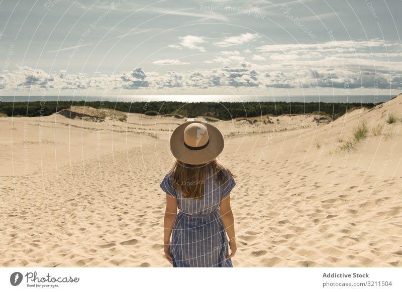 erwachsene Frau in Freizeitkleidung und Strohhut stehend, die sich auf einer Sanddüne vergnügt Sommer verträumt Düne heiß Tourismus modern Klarer Himmel Kleid