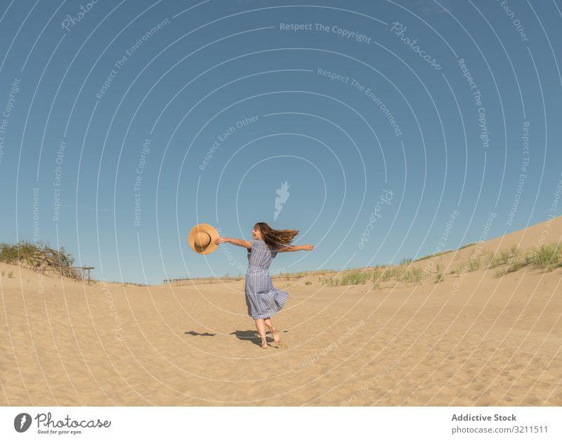 erwachsene Frau in Freizeitkleidung und Strohhut läuft und sich auf einer Sanddüne amüsiert Sommer verträumt Düne heiß Tourismus modern Klarer Himmel Kleid