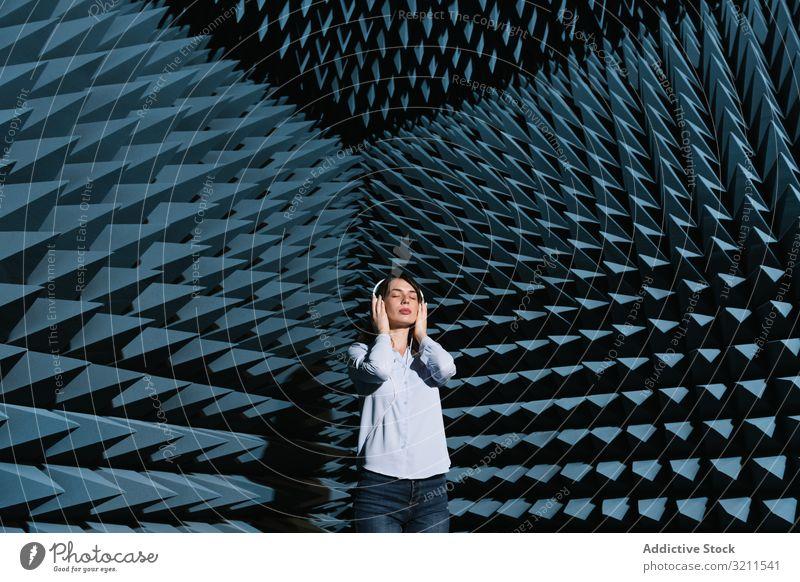 Frau im Schallzimmer, die Musik hört Klang Raum zuhören genießen akustisch sich[Akk] entspannen Zeitgenosse Kopfhörer modern schön jung Technik & Technologie