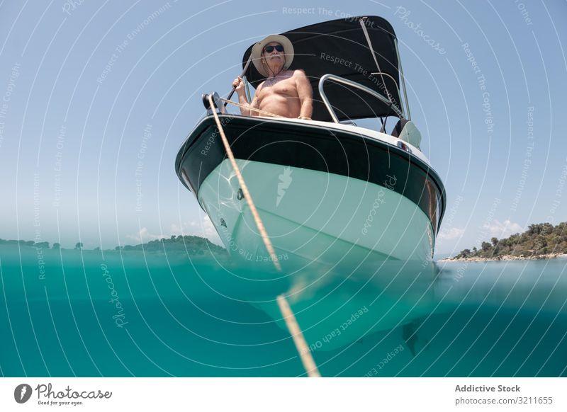 Mann segelt im Boot in klarem türkisfarbenen Wasser Segeln Jacht älter Urlaub Sommer nautisch reisen MEER Reichtum Freizeit halkidiki Matrosen Griechenland