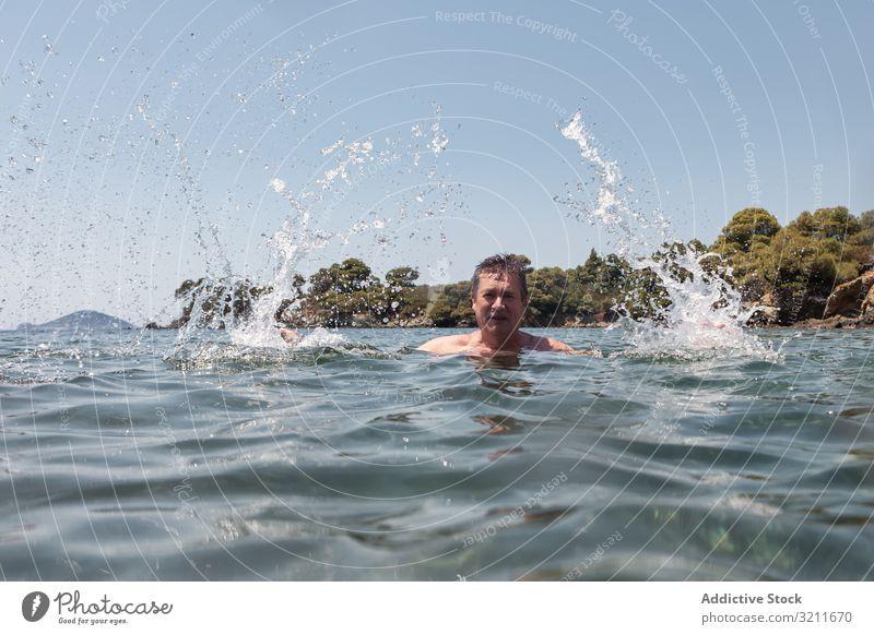 Aktive Senioren schwimmend und plantschend im Wasser Mann Schwimmsport platschen älter in den Ruhestand getreten reisen Schnurrbart Urlaub halkidiki