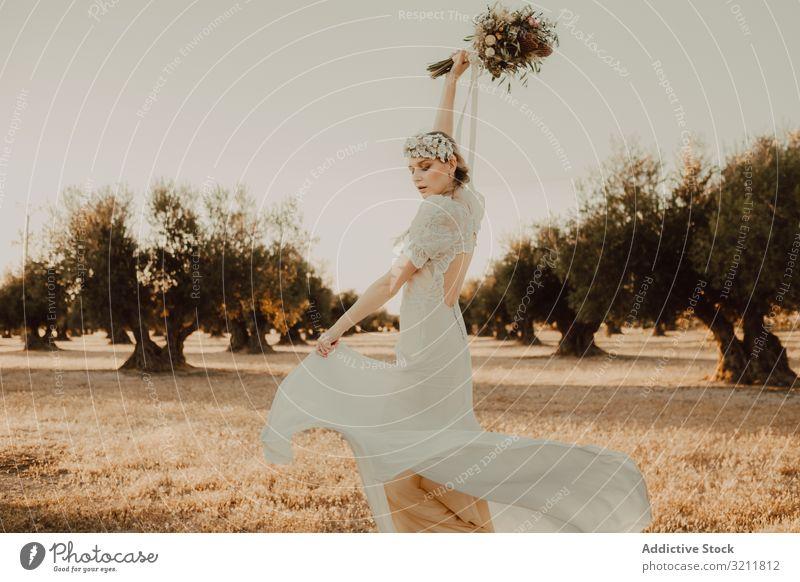 Zufriedene Frau im Kleid mit offenem Rücken, die die Hände mit Blumenstrauss hebt Blumenstrauß Braut Boho Spitze Totenkranz schön Stil Angebot sinnlich