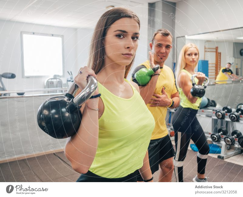 Athleten mit Kettlebells in der Turnhalle Klasse Übung Training Fitnessstudio heben Sport Stärke über Kopf Kraft Trainer Menschengruppe Wohlbefinden Vitalität
