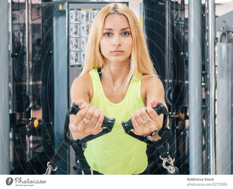 Schlanke Frau übt auf Widerstandstrainerin Athlet Übung Seil Widerstandskraft Trainerin Truhe Seilrolle Fliege Fitnessstudio Sportbekleidung entschlossen