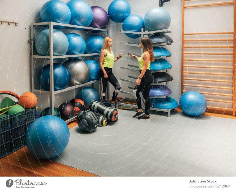 Sportlerinnen, die im Fitnessstudio in der Nähe des Geräteträgers stehen modern Ablage Pause Training Zentrum Team Club Ball Klasse Frauen Motivation Stärke