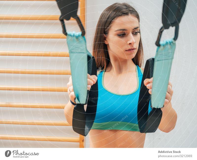 Training junger Frauen in der Turnhalle Sportlerin Suspension Seil Übung trx Körpergewicht erhängen physisch Athlet Fitnessstudio Motivation Stärke Kraft modern