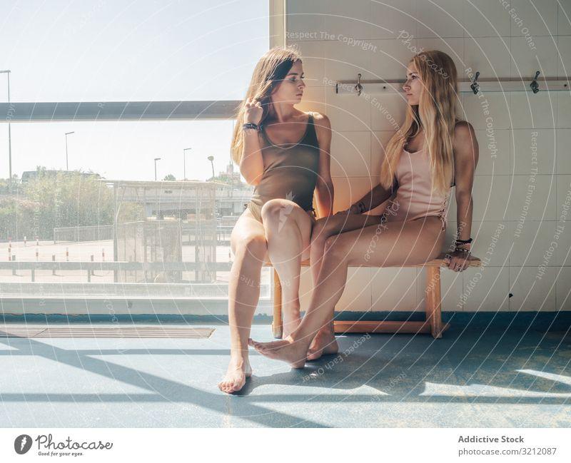 Junge Frauen in der Umkleidekabine eines Schwimmbades Ankleidezimmer Pool Badebekleidung Fitness sinnlich Bank Zusammensein Freund Angebot sitzen jung