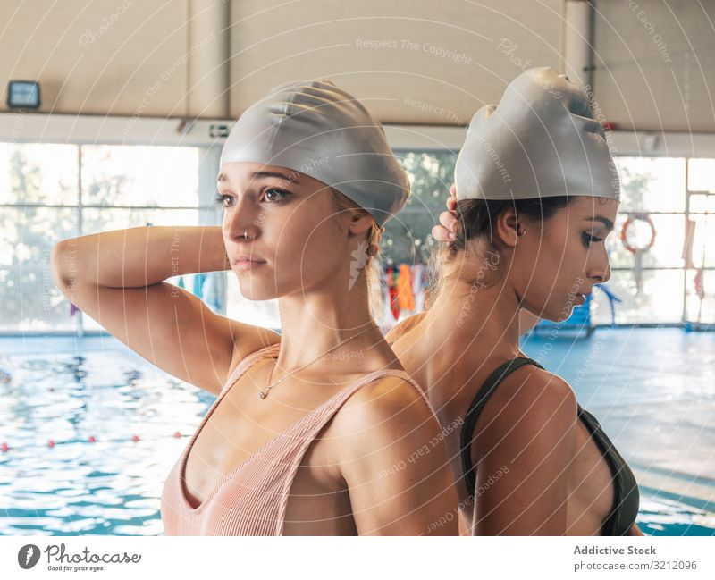Schlanke Damen mit Badekappe im Schwimmbad Frauen Schwimmsport Pool Verschlussdeckel jung Team Wasser Fitnessstudio Freund Einrichtung Rücken an Rücken Schutz