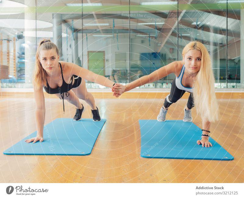 Junge Sportlerinnen auf dem Seitenbrett Athlet Übung Schiffsplanken Fitnessstudio Arme Team heben Frauen Wellness Training Zusammensein Gleichgewicht abstützen