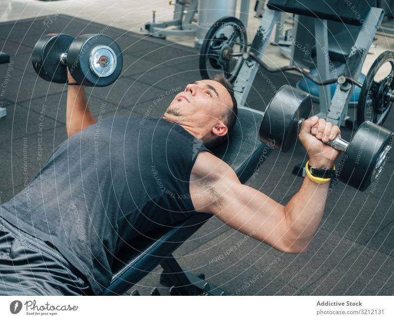 Starker Mann übt mit Hanteln auf der Bank Athlet Kurzhantel Lügen heben Presse Übung Bodybuilding Fitnessstudio fokussiert Motivation Ausdauer männlich Training