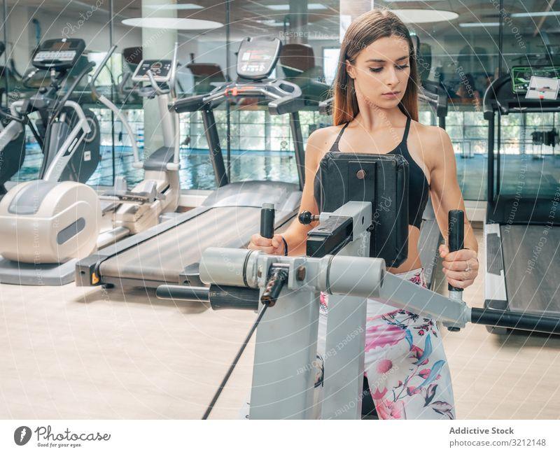 Starke Frau auf Reihenmaschine Übung Maschine Fitnessstudio Training Sport Athlet Stärke Kraft Rücken modern passen jung Gesundheit Wellness Wohlbefinden