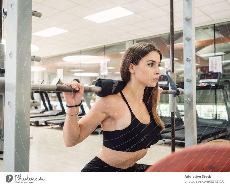 Junger Athlet hockt mit Langhantel Frau Kniebeuge Curl-Hantel Bodybuilding Fitness Übung Fitnessstudio Ausdauer Training Sport Stärke Kraft modern Dame passen