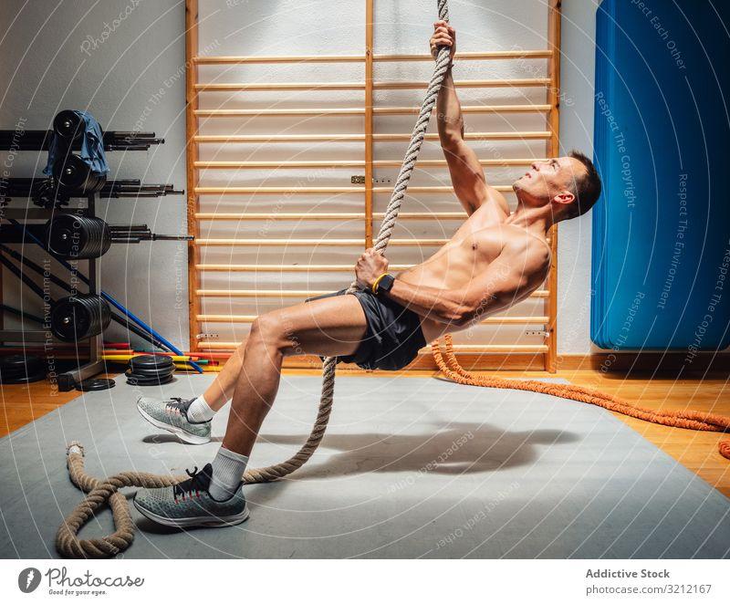 Muskelsportler klettert Seil in Turnhalle Athlet Aufstieg Fitnessstudio Übung Mann Training Sport Stärke Kraft anstrengen physisch modern fokussiert Gerät