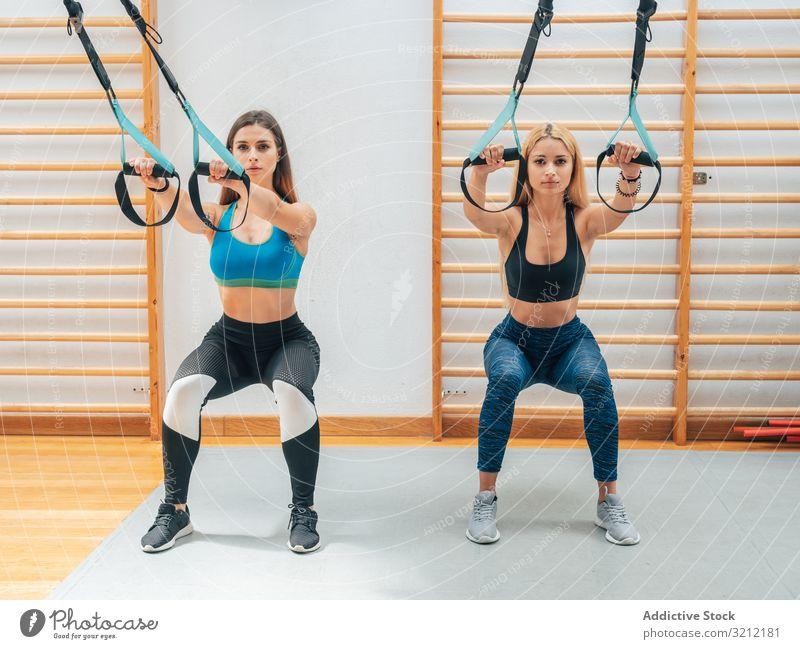 Starke Damen hocken mit Seilen Sportlerinnen Training Suspension Fitness Kniebeuge Athlet Übung trx Wohlbefinden Tatkraft Gerät Sportbekleidung Fitnessstudio