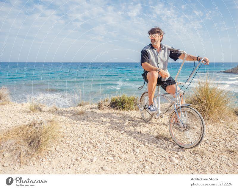 Mann radelt auf Sandstrandhügel Fahrrad sandig Seeküste Urlaub Glück Fahrradfahren Sommer winken aktiv Lifestyle Feiertag Ausflug energetisch reisen Reise