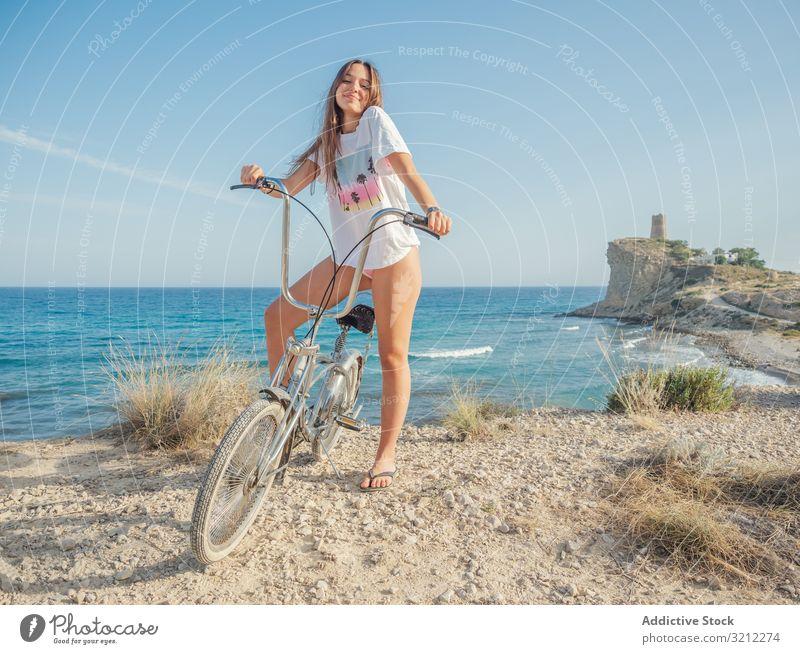 Frau radelt auf Sandstrandhügel Fahrrad sandig Seeküste Urlaub Glück Fahrradfahren Sommer winken aktiv Lifestyle Feiertag Ausflug energetisch reisen Reise jung