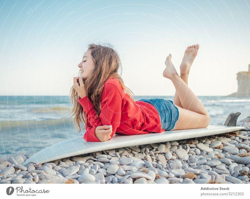 Fröhliche Frau mit gekreuzten Beinen auf einem Surfbrett liegend Erholung Lächeln Meer Lügen Feiertag hübsch Sport Strand heiter schön Glück attraktiv Urlaub