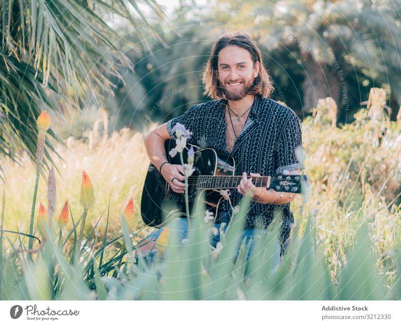 Hipster-Mann auf der Wiese mit Gitarre Musiker Sitzen Dschungel Spielen Abenteuer Ausflug Sommer Lifestyle besinnlich männlich akustisch jung Entertainment