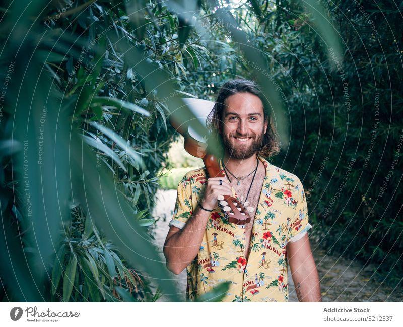 Hipster-Mann im Dschungel mit Ukulele Musiker reisen Abenteuer Ausflug Sommer Lifestyle besinnlich männlich Urlaub Freiheit jung Tourist farbenfroh lässig