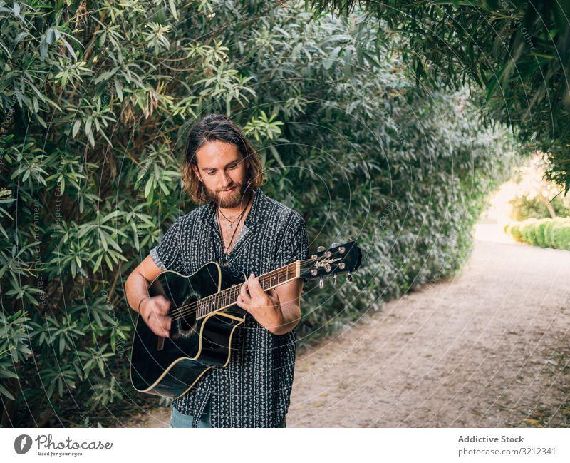 Hipster-Mann im Dschungel mit Gitarre Musiker Spielen Abenteuer Ausflug Sommer Lifestyle besinnlich männlich akustisch jung Entertainment Freizeit üben Natur