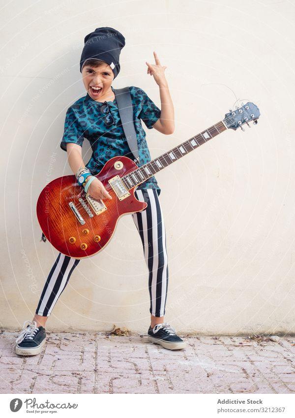 Energisches Kind gestikulierend Rock haltend Gitarre Junge Spielen Rockstar Felsen farbenfroh Kindheit Mode Zeichen Künstler Musiker festlich Lachen wenig