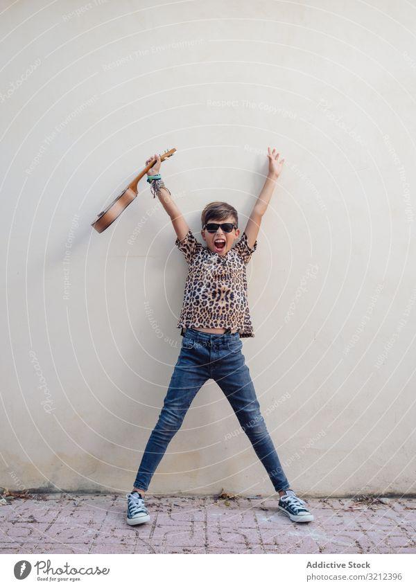 Aufgeregtes Kind hebt die Hände mit der Ukulele Spaß haben Junge Spielen dekorativ Instrument farbenfroh Musical niedlich Entertainment üben schön Sonnenbrille
