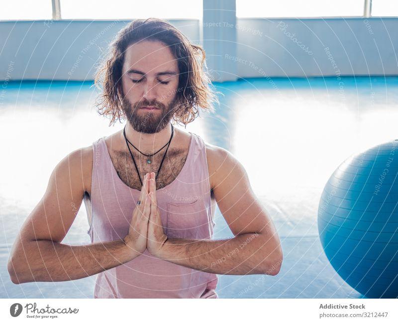 Männlich meditierend im geräumigen Raum Mann Fitnessstudio Lotos sich[Akk] entspannen Yoga Vitalität Zen Harmonie Übung Asana Sport Beine gekreuzt jung