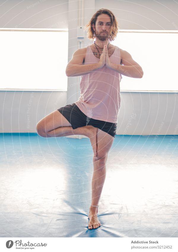 Mann macht Yoga in geräumigem Raum Fitnessstudio sich[Akk] entspannen Vitalität Zen Harmonie Übung Asana Sport jung Windstille Frieden männlich bärtig Glück