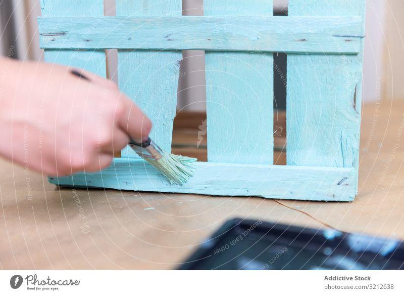 Frau malt Holzkiste in blauer Farbe mit Pinsel Anstreicher Bürste gemalt farbenfroh Design rustikal Kunst hölzern Handwerk Kasten dekorativ Künstler Stil