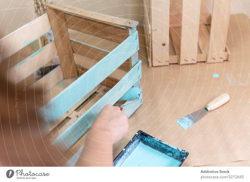 Frau malt Holzkasten in blauer Farbe mit Walze Anstreicher Rolle gemalt farbenfroh Design rustikal Kunst hölzern Handwerk Kasten dekorativ Künstler Stil