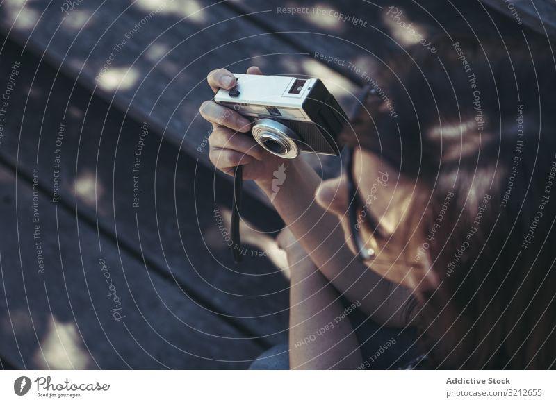 Frau mit Fotokamera sitzt und schaut an einem sonnigen Tag mit Natur Bank professionell lässig Freizeit Lifestyle Fotografieren Feiertag Sommer Hobby digital