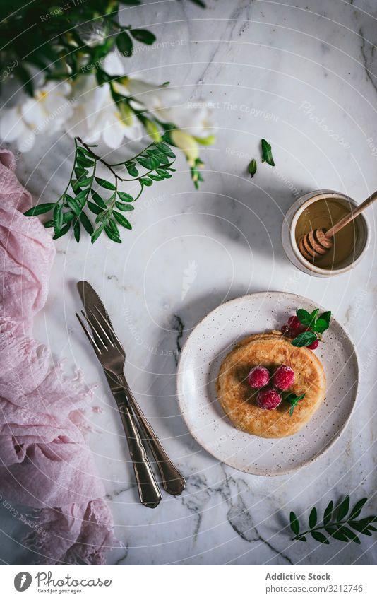 Pfannkuchen mit frischen Himbeeren auf Teller gold-braun Minze Murmel Tischplatte Frühstück geschmackvoll Blätter stylisch weiß Servieren Garnierung Dessert
