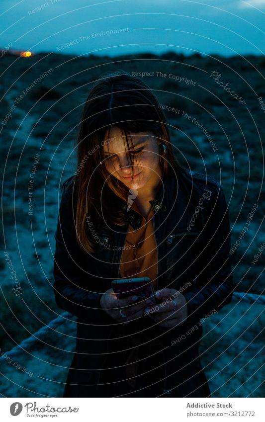 Frau surft mit ihrem Smartphone nachts im Freien Lederjacke Handy Browsen Nacht schön Mitteilung Internet Anschluss jung Nachricht Text Technik & Technologie