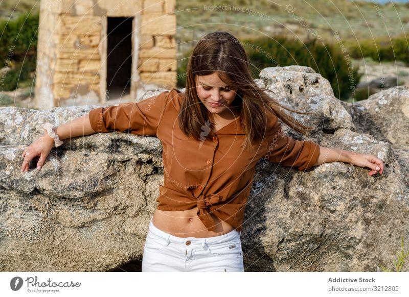Frau steht neben großem Felsen Stein Glück Stehen Natur sorgenfrei Feld Land Sommer Lächeln schön attraktiv genießen Freiheit Abenteuer lässig Tourismus Ansicht