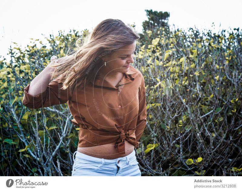 Glückliche Frau steht vor Büschen Natur heiter Sommer sorgenfrei Feld Land Lächeln schön attraktiv Hand auf Kopf genießen Freiheit Abenteuer lässig grün