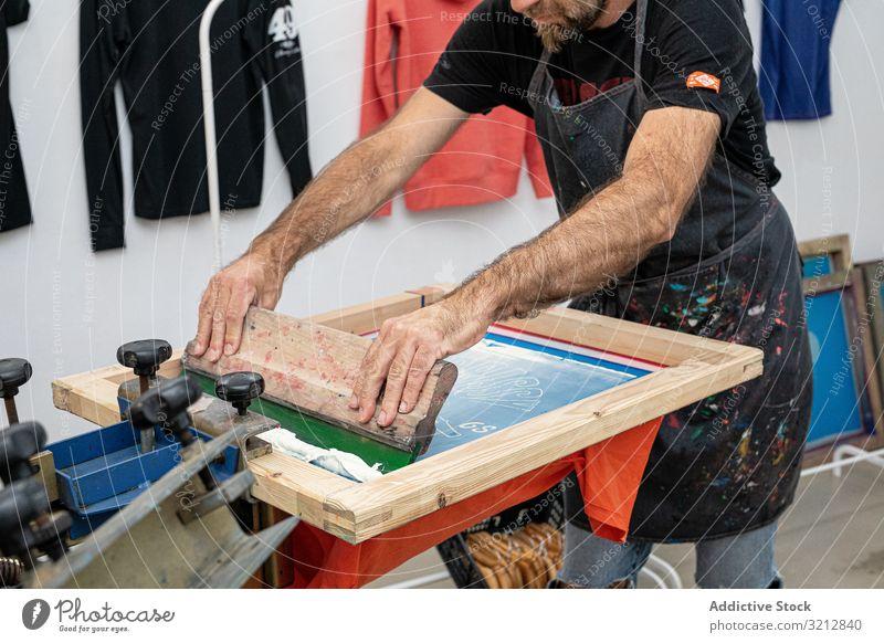 Männlicher Künstler erstellt Druck auf T-Shirt Meister Bildschirm drucken Siebdruck Serigraphie erschaffend Werkstatt Hobby Staffelei dreckig Schürze Stil Farbe