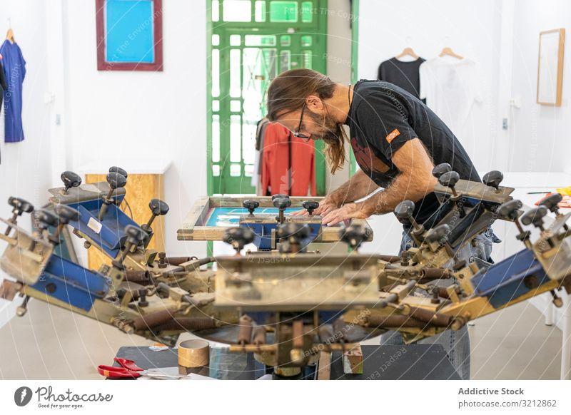 Künstlerischer Siebdruck in der Werkstatt Bildschirm drucken T-Shirt Kunstwerk Meister Hobby Serigraphie kreativ Staffelei Malerei Zeichnung männlich