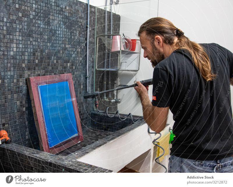 Künstlerin bereitet Siebdruck für Serigraphie vor Werkstatt drucken Bildschirm vorbereiten erschaffend Mann blau Hobby Staffelei Farbe Zeichnung männlich